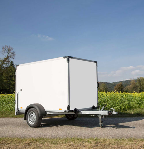 Small enclosed trailer sitting on a gravel road
